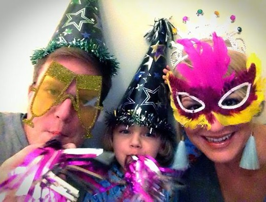 Fred, Kim and Knox Bishop in masks, glasses and hats blowing horns for Happy New Year