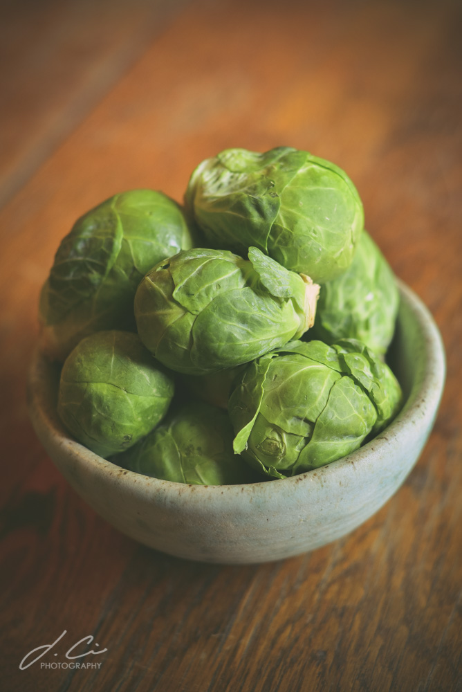 Raw brussels sprouts in a bowl on a wooden table