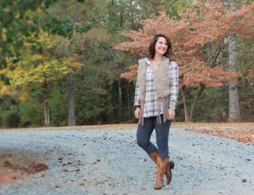 Kim Bishop from Crockpot Empire is wearing a tan fringe shearling vest with a plaid shirt and Cowboy boots from Honey Butter Boutique