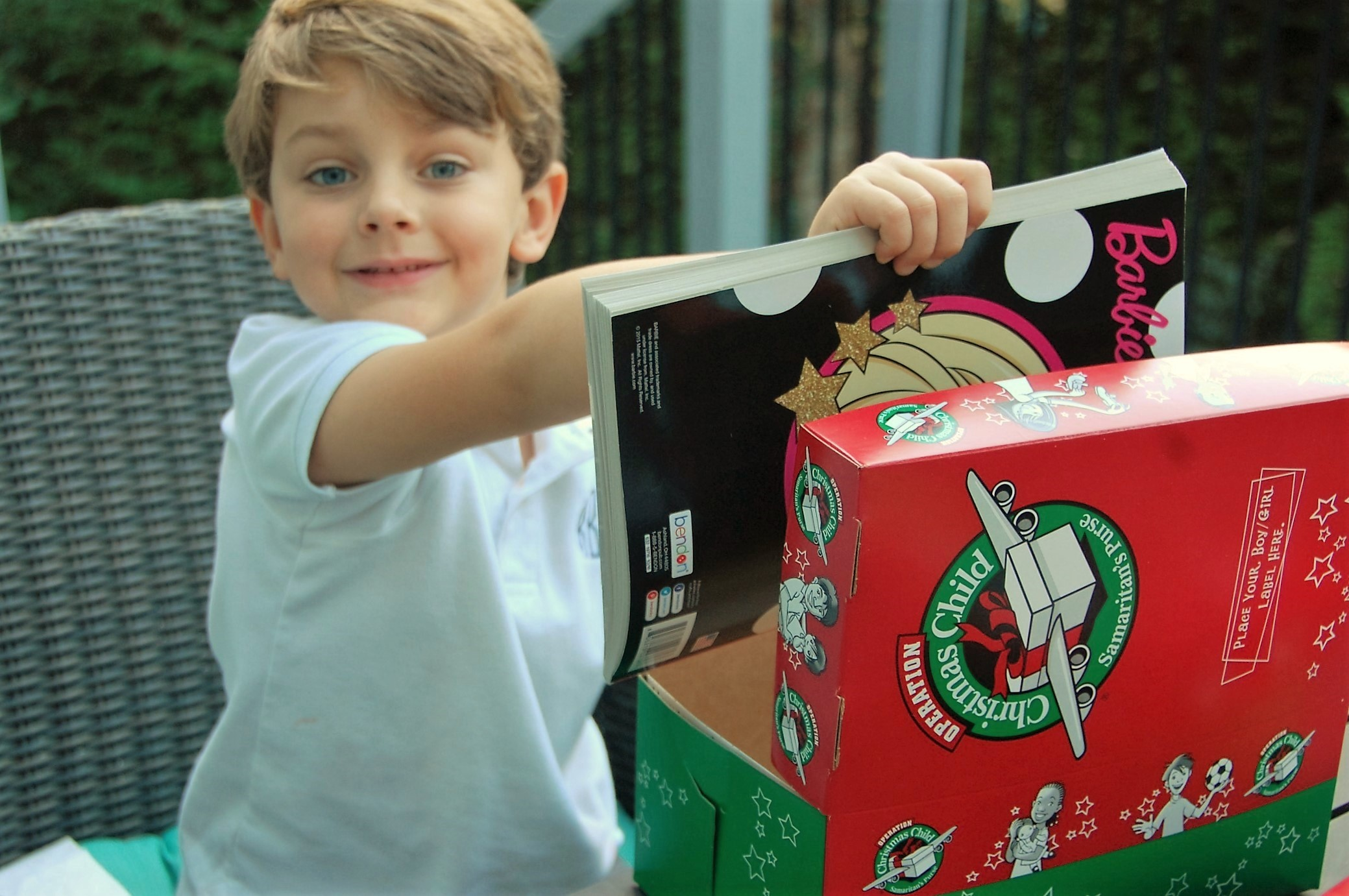 Knox Bishop supports Operation Christmas Child and puts a Barbie magazine along with many other toys and toiletries into his Samaritan's Purse Box by Crockpot Empire