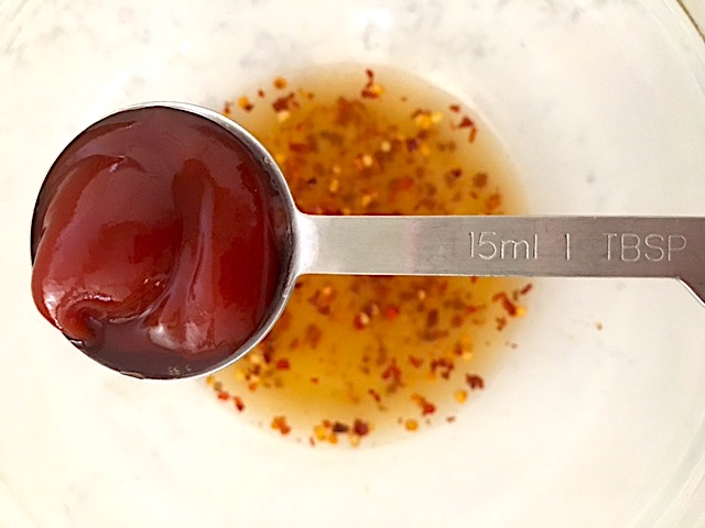 ketchup in a measuring spoon goes into marinade for crockpot bourbon chicken