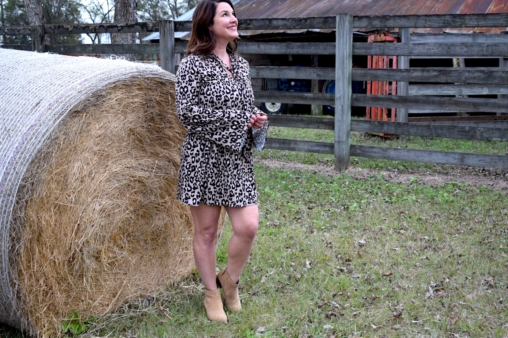 Kim Bishop of Crockpot Empire wearing a Fabrik leopard print dress on a farm in front of a hay bale
