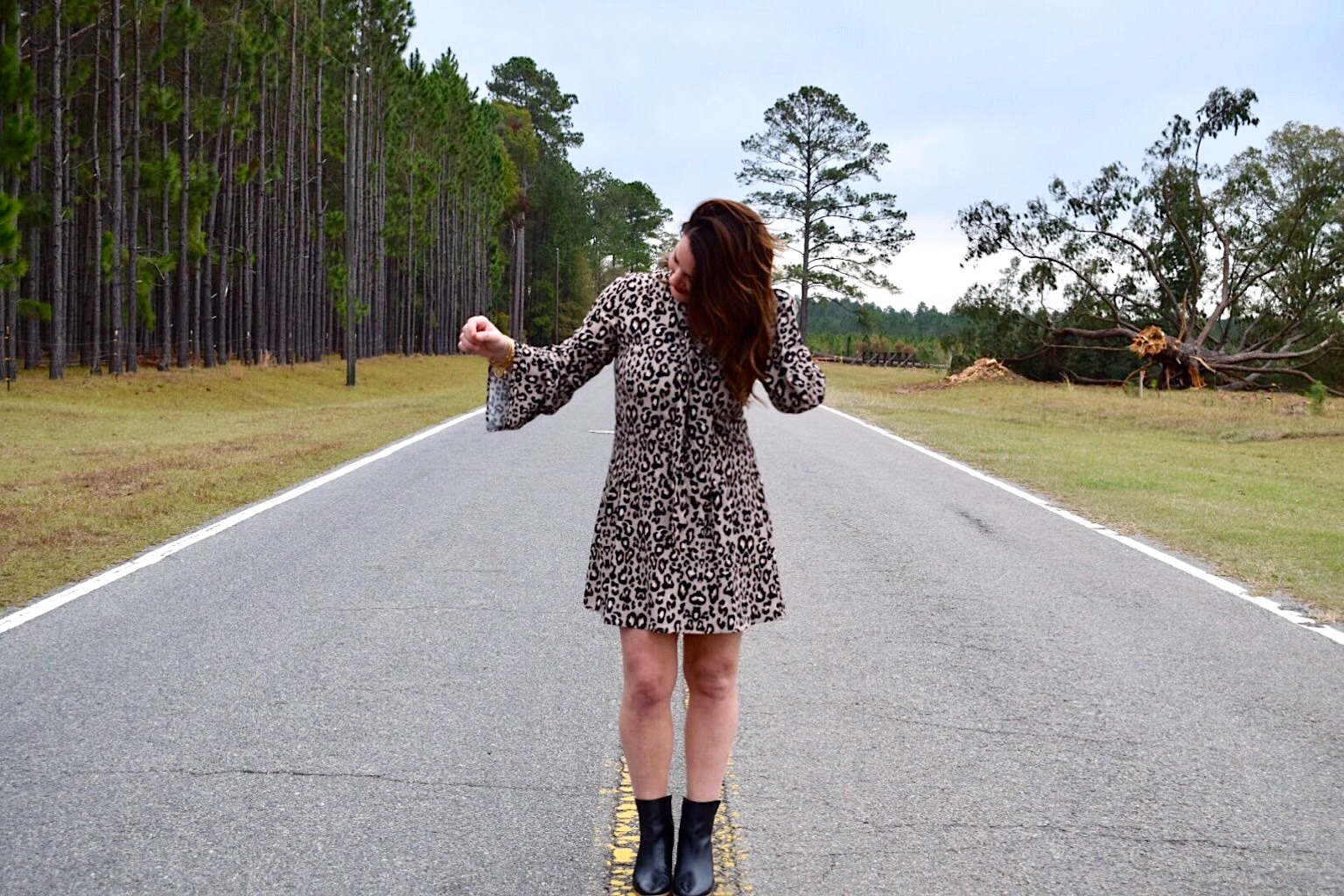 Kim Bishop on country two lane country road wearing a leopard print dress with black booties