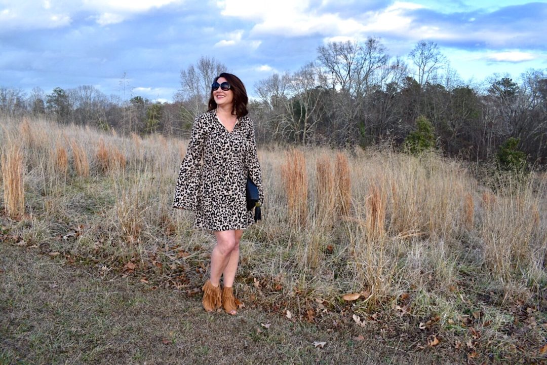 Kim Bishop of Crockpot Empire wearing a Fabrik leopard print dress with bell sleeves paired with Baublebar tassel earrings and a black India Hicks leather tassel clutch and cognac fringe booties