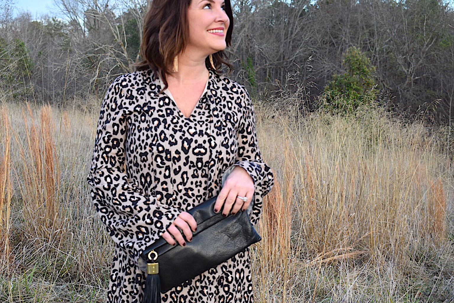 Kim Bishop of Crockpot Empire wearing a Fabrik leopard print dress with bell sleeves paired with Baublebar tassel earrings and a black India Hicks leather tassel clutch