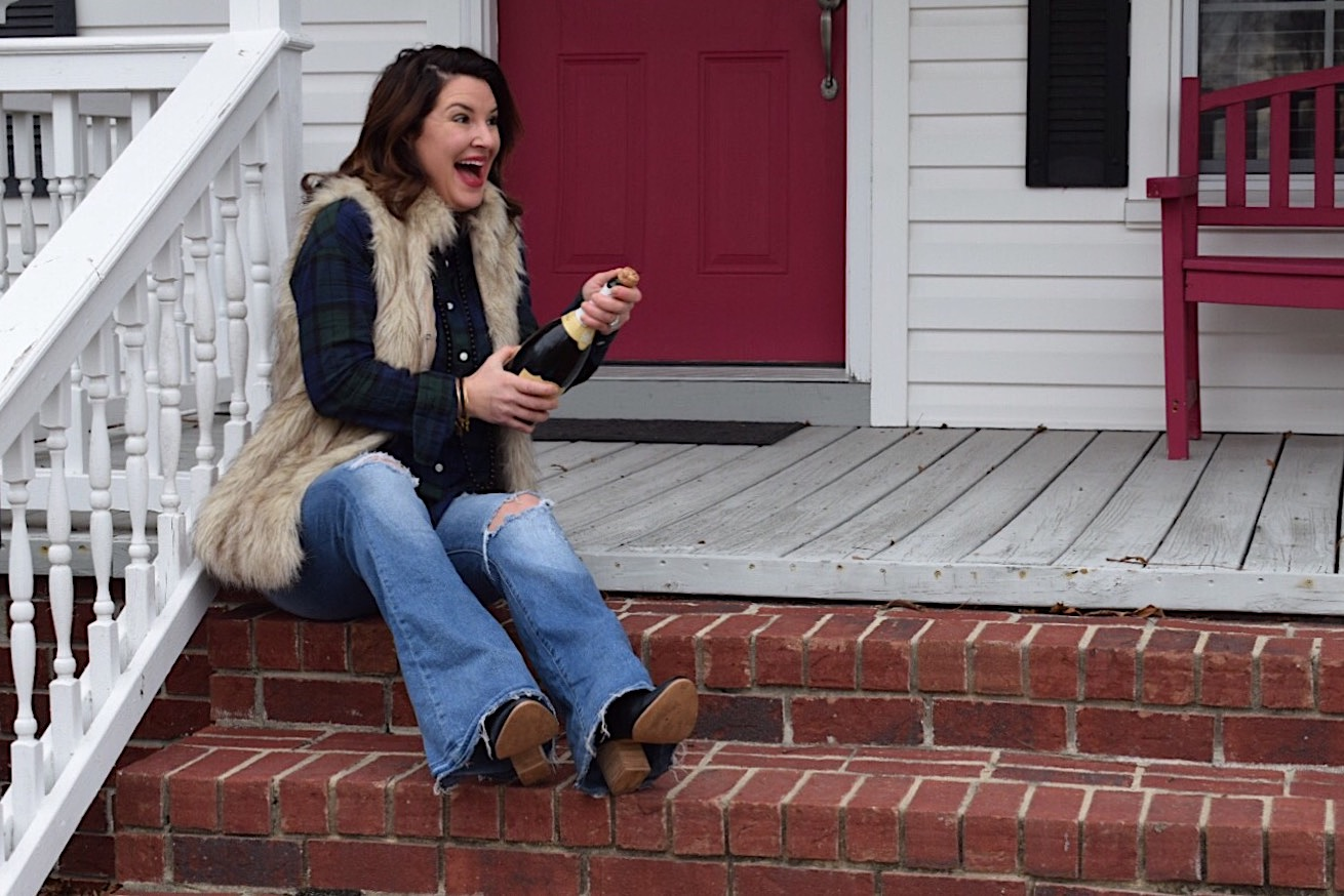 New Year, Same God - Kim Bishop popping champagne on the porch in a plaid shirt with a faux fur vest
