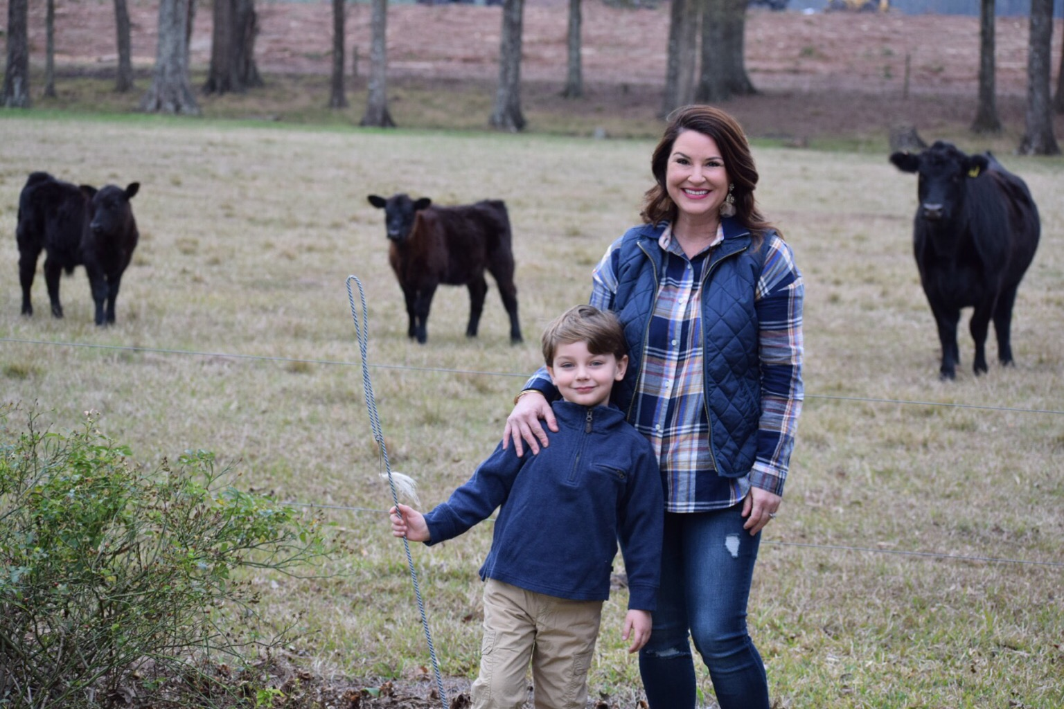 New Year, Same God - Knox and Kim Bishop on a cow farm - Plaid shirt with navy puffer vest