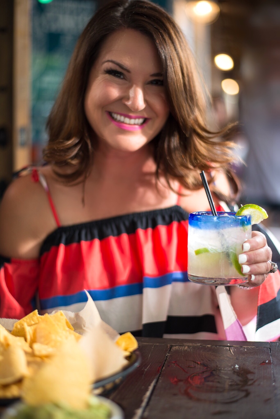 Kim Bishop Crockpot Empire drinking a margarita in Nicholas Amalfi Stripe Cold-Shoulder dress