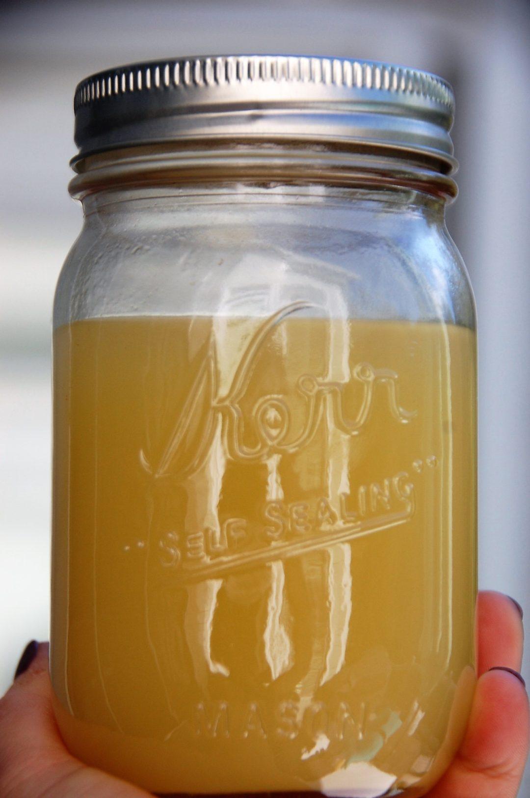 healthy crockpot chicken stock in a Kerr Mason jar by Crockpot Empire