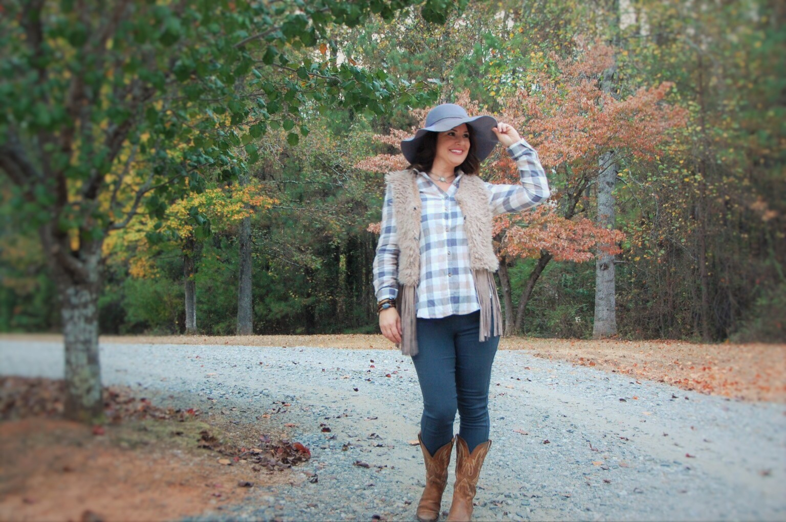 Kimberly Bishop from Crockpot Empire in a southern look by Honey Butter Boutique. A shearling fringe vest, plaid shirt, and cowboy boots