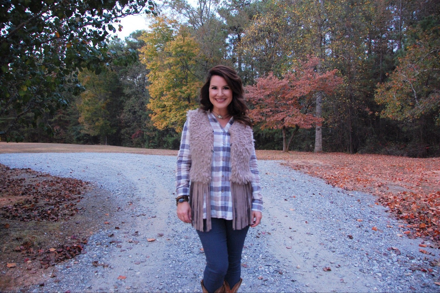 The outfit from fabulousgood.com is a shearling fringe vest paired with a plaid shirt, denim and cowboy boots