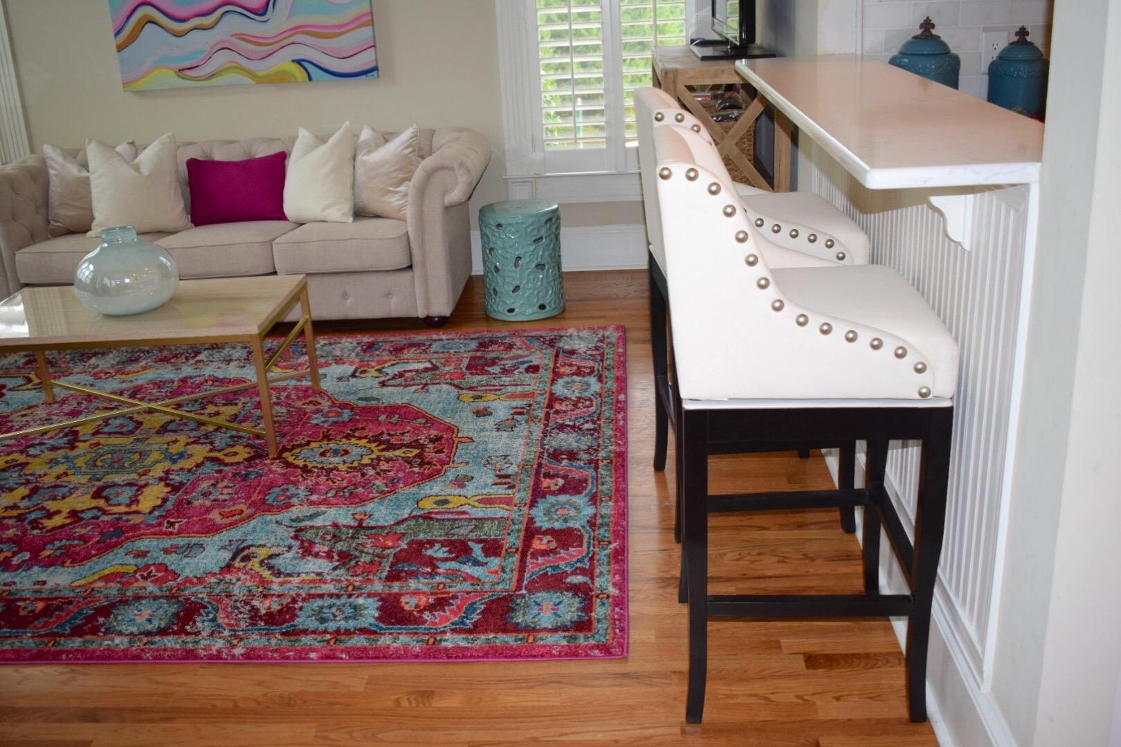 Pink Rug with white Ballard Design Nailhead trim bar stools in kitchen