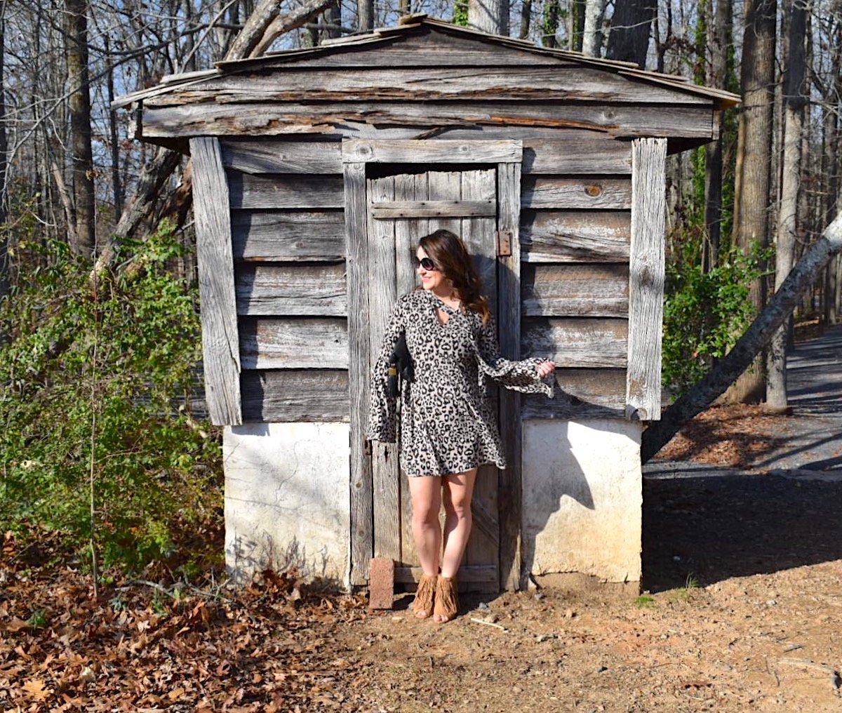 Kim Bishop of Crockpot Empire wearing a Fabrik leopard print dress with bell sleeves paired with Baublebar tassel earrings and a black India Hicks leather tassel clutch in front of a wooden shed