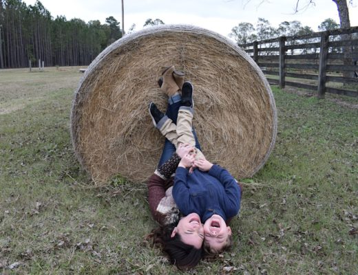 Kim and Knox Bishop with their legs on a hay bale upside down laughing
