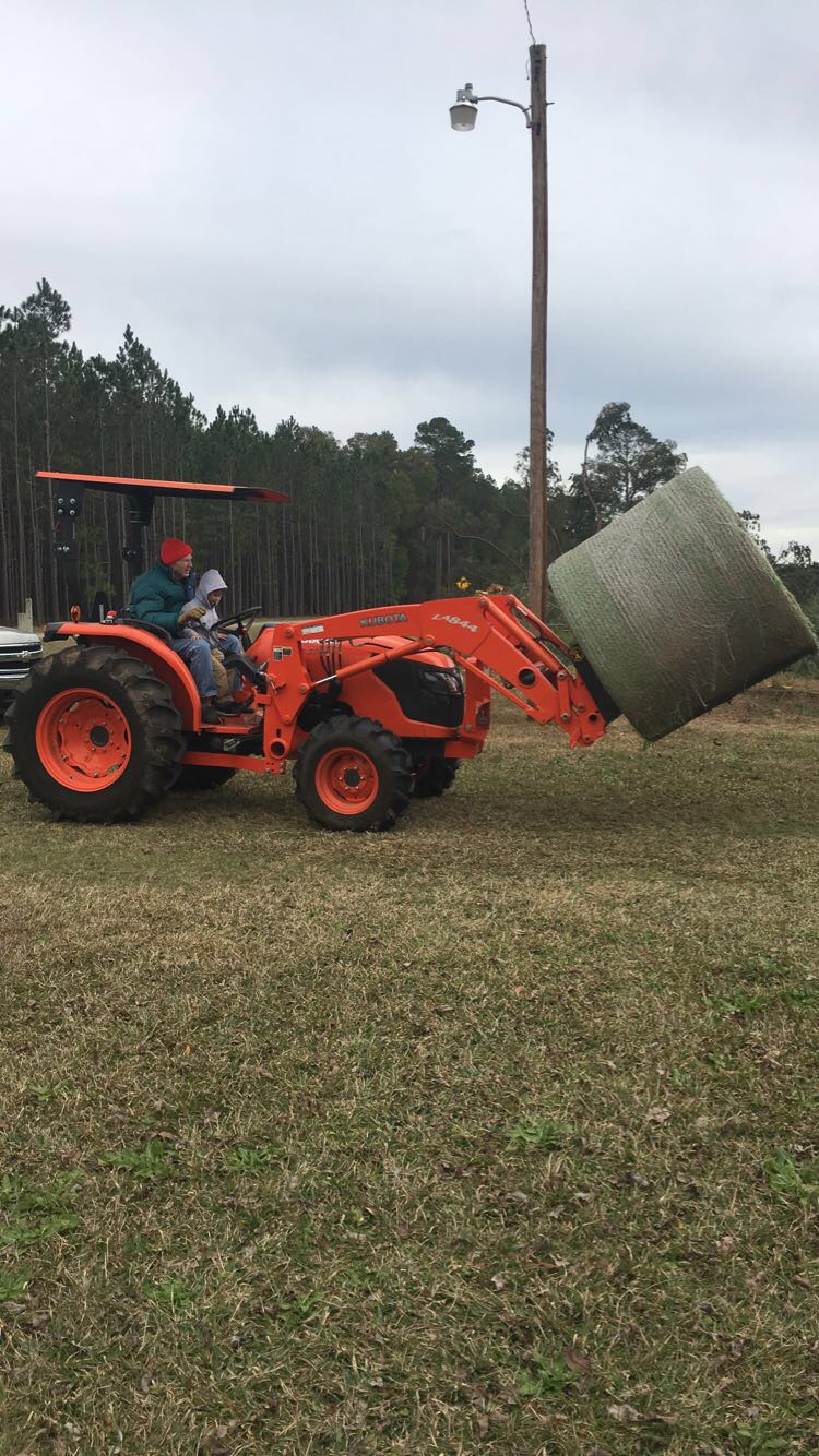 New Year, Same God - Knox and PaPa Bishop riding on the Kubota Tractor with a hay bail to feed the cows