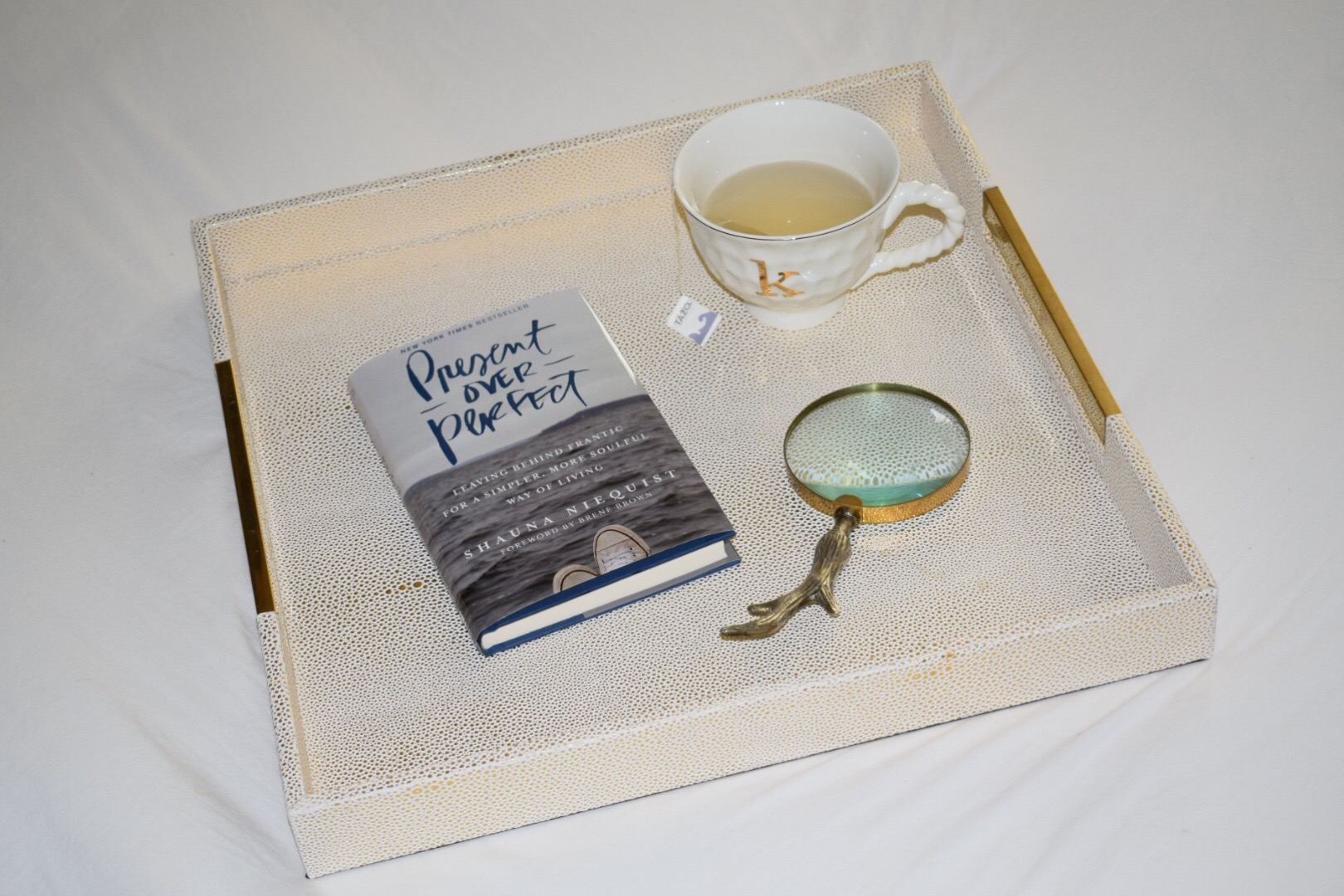Present Over Perfect by Shauna Niequist on gold tray with antler magnifying glass