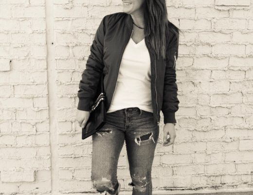 Black and white photo of olive bomber jacket with canvas espadrilles, destroyed denim and a white tee shirt