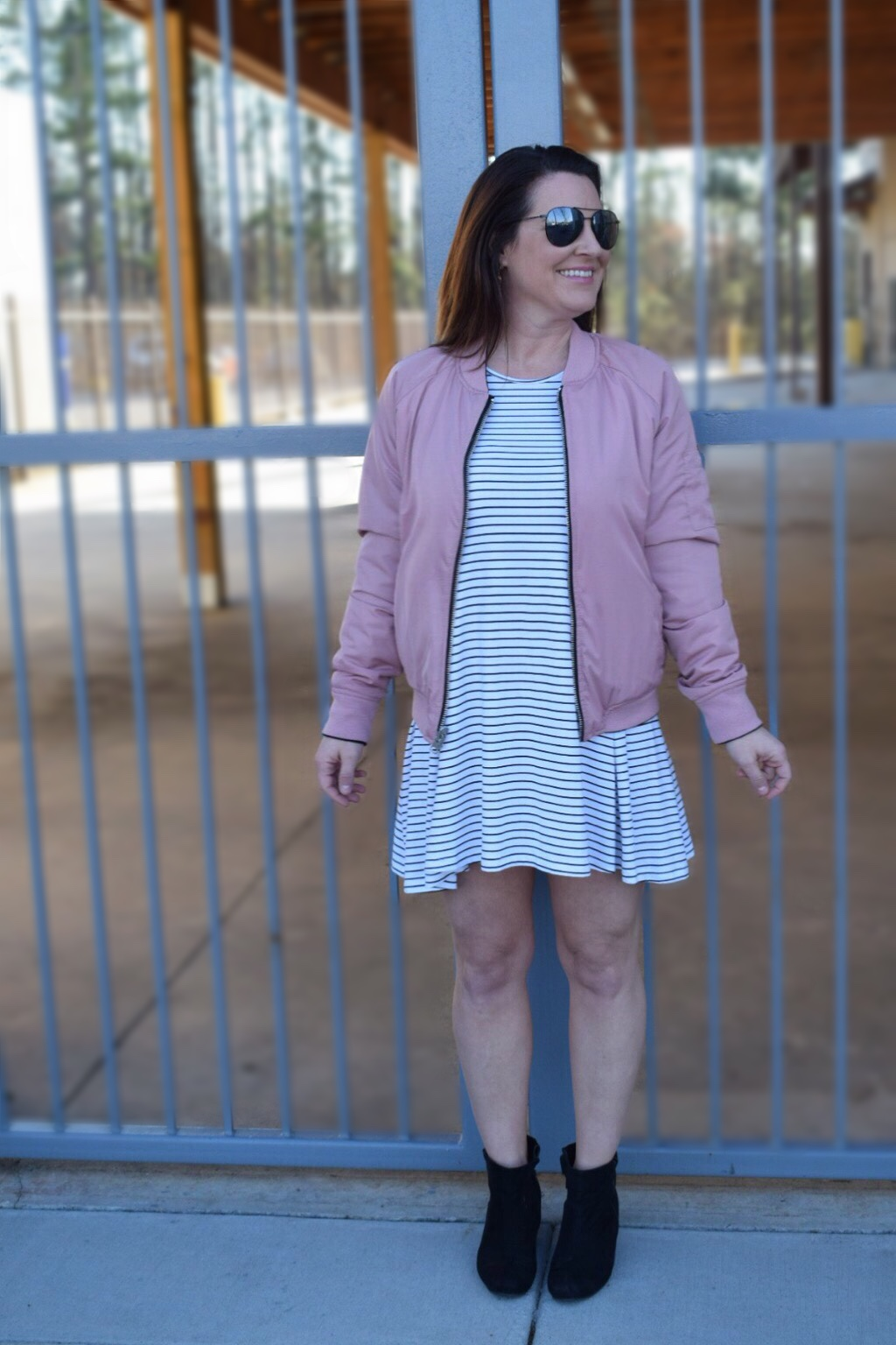 Blush Bomber Jacket with a black and white striped t shirt dress and black booties