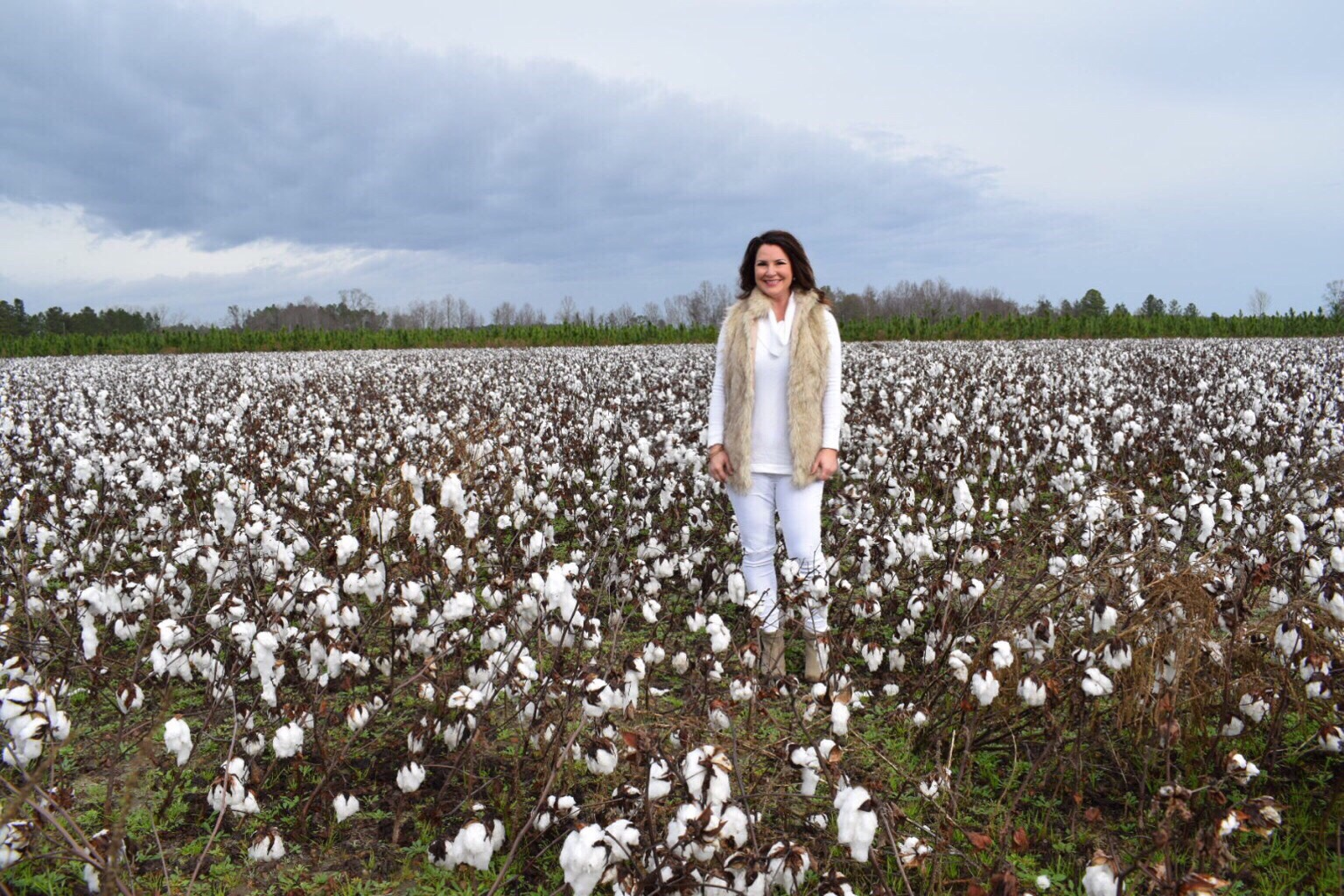 Kim Bishop in the middle of a cotton field
