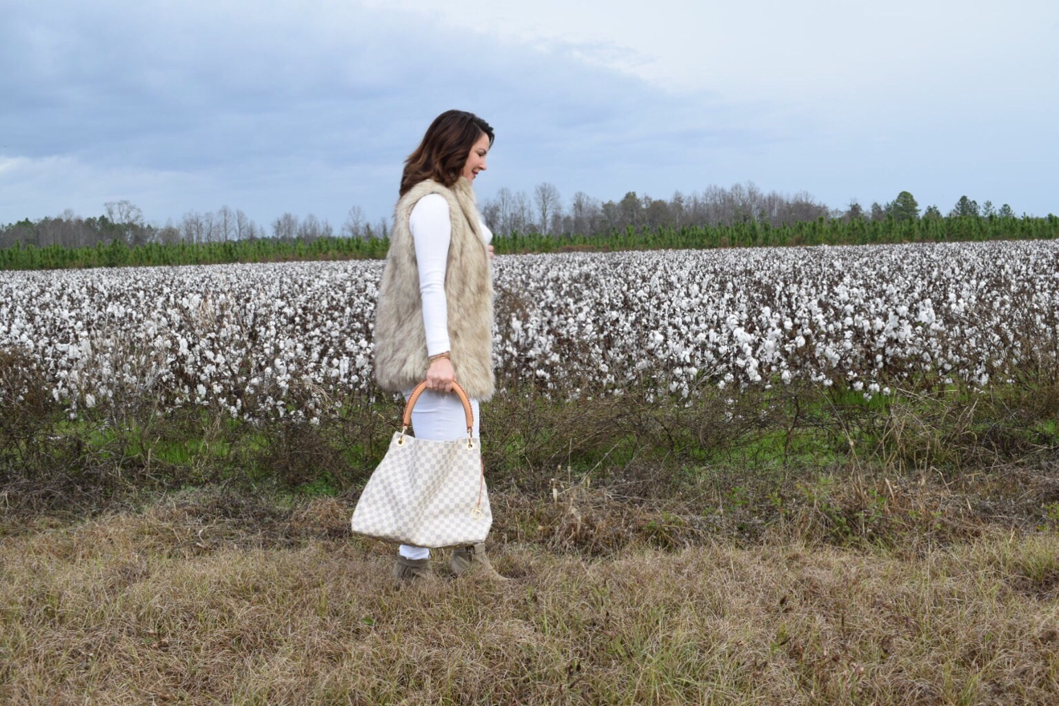 Kim Bishop walking in a cotton field in winter white and faux fur vest with Luis Vuitton Damier Azur Artsy bag