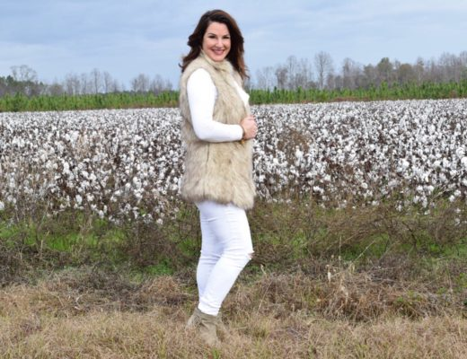 Kim Bishop in a cotton field wearing a faux fur vest, white skinny jeans and Sam Edelman booties