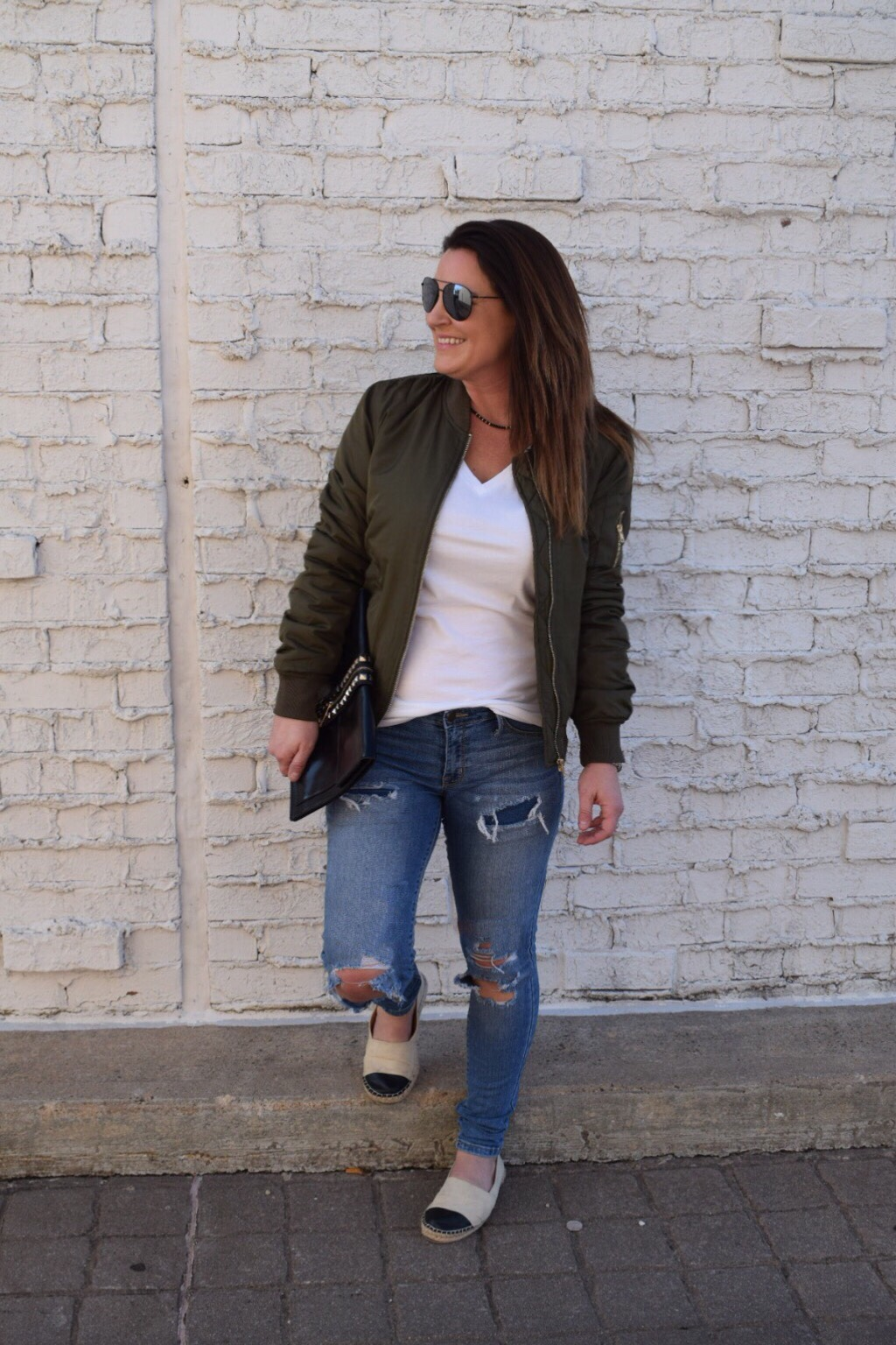 Olive bomber jacket with destroyed denim a white tee, canvas espadrilles and black aviators