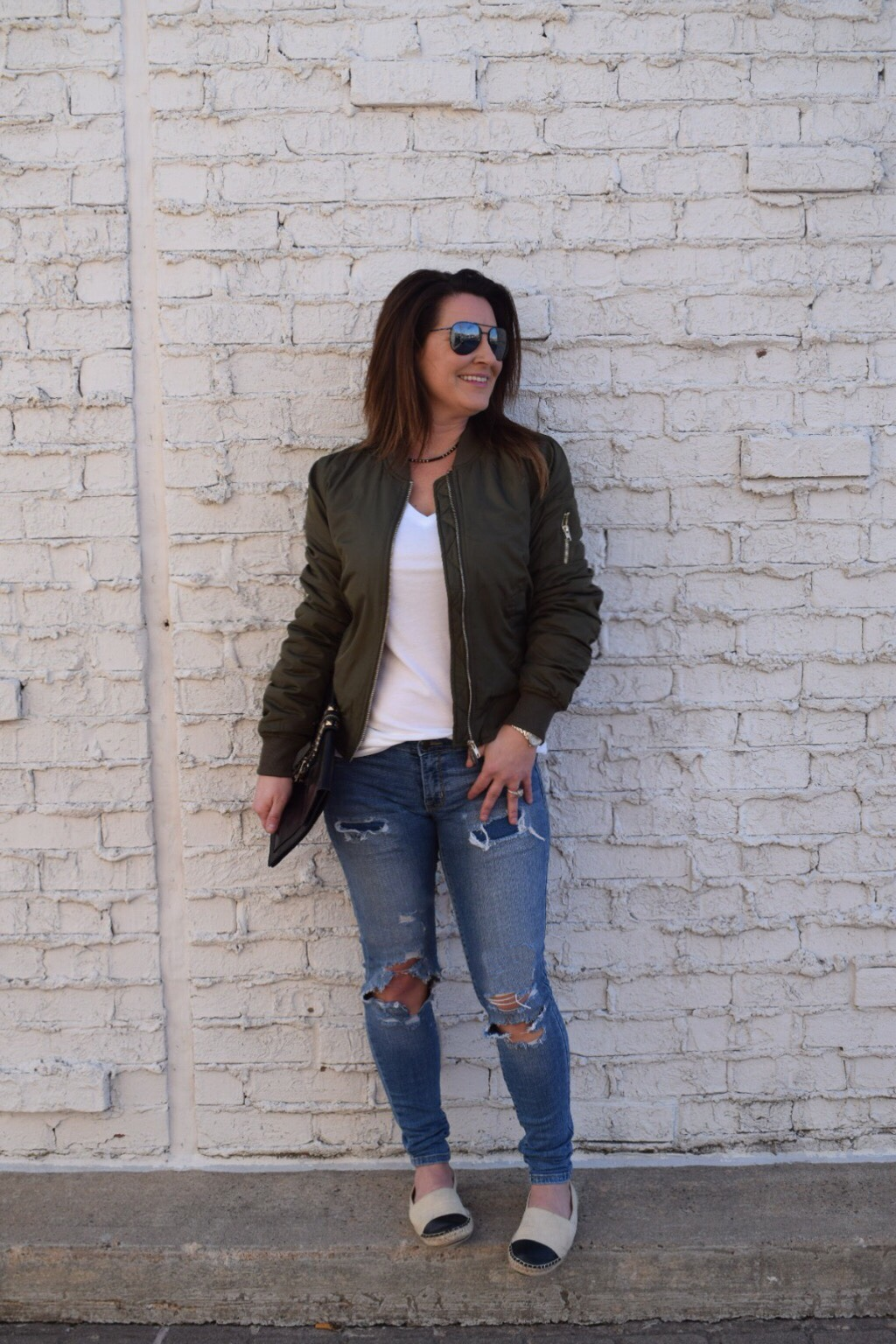 Olive bomber jacket with destroyed denim a white tee canvas cream espadrilles and black aviators