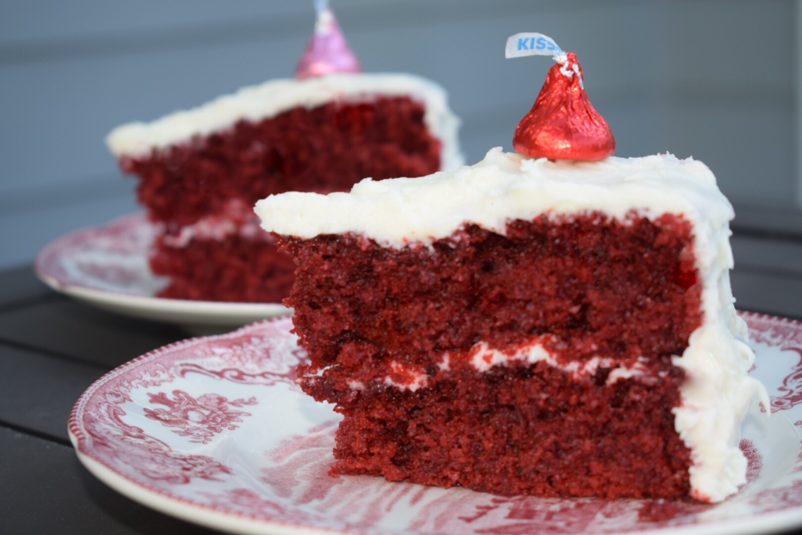 Two slices of red velvet cake on toile Johnson Bros plates topped with pink and red chocolate Hershey kisses