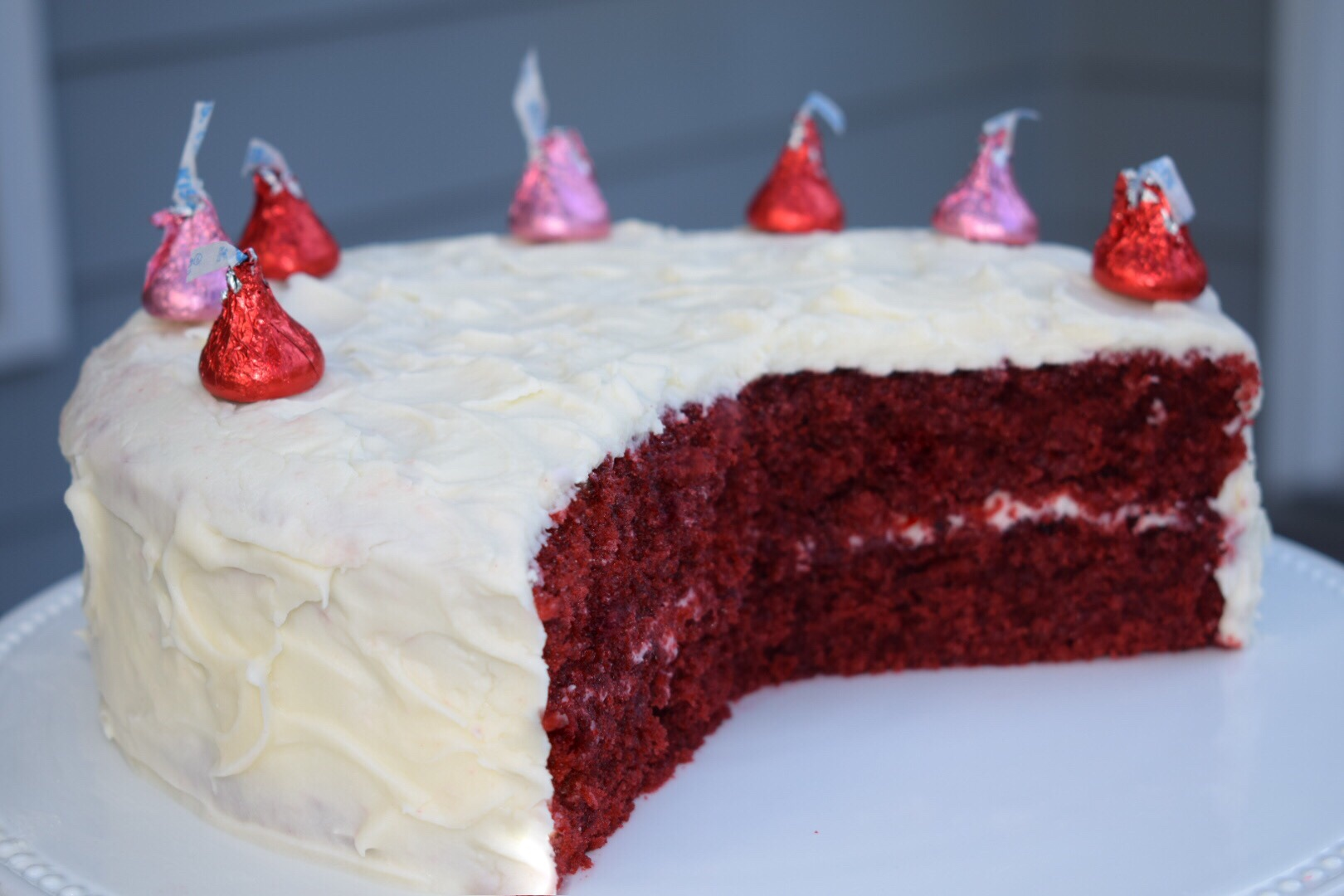 Red Velvet Cake cut into with white cream cheese frosting and topped with pink and red chocolate Hershey kisses
