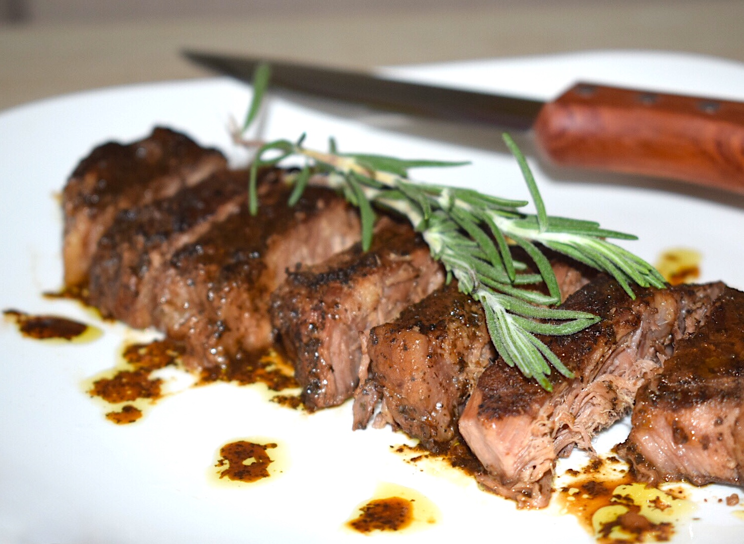 The best steak marinade in existence recipe used with the steak cut up on a plate with a steak knife
