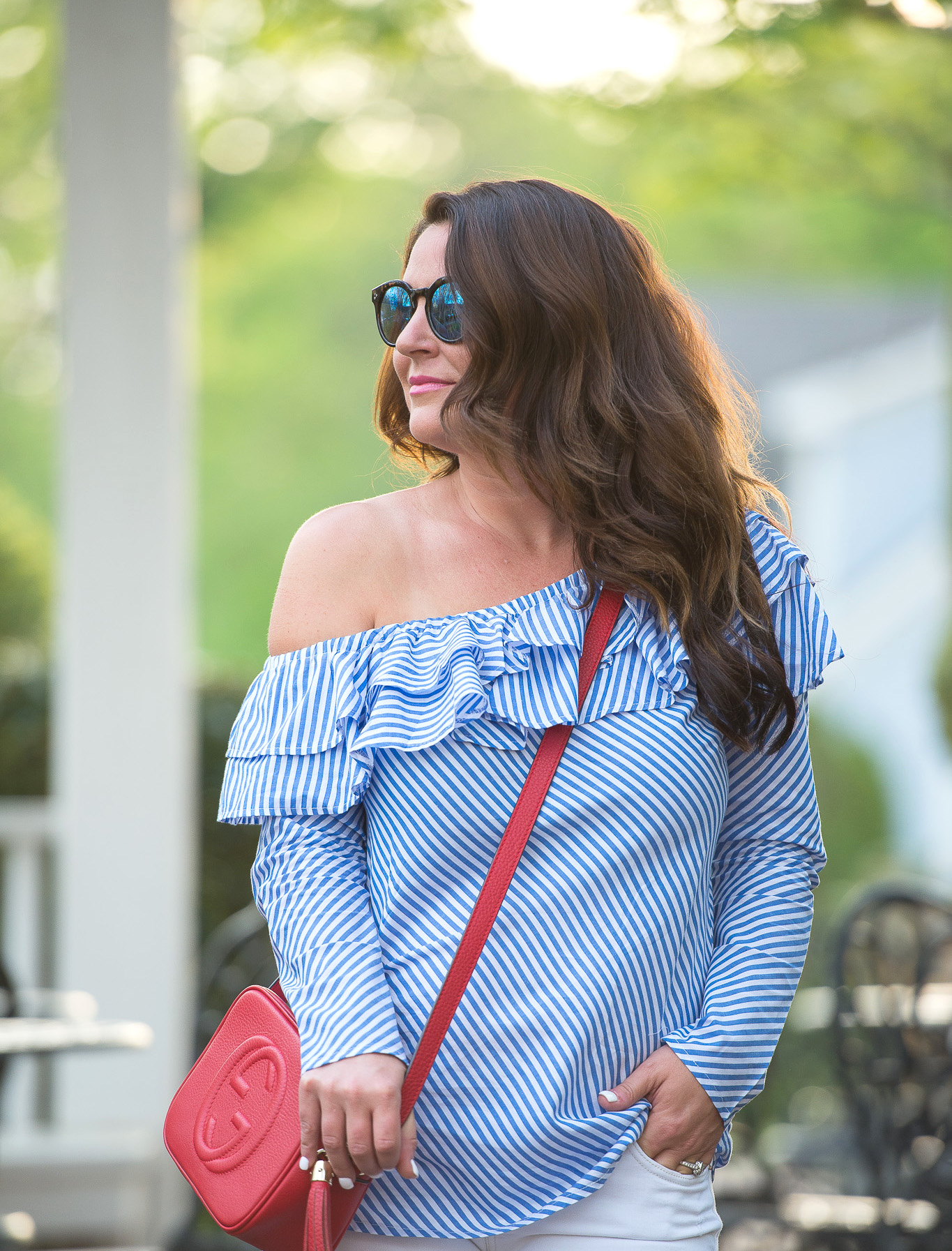 Kim Bishop in a blue striped ruffle one shoulder top and red purse