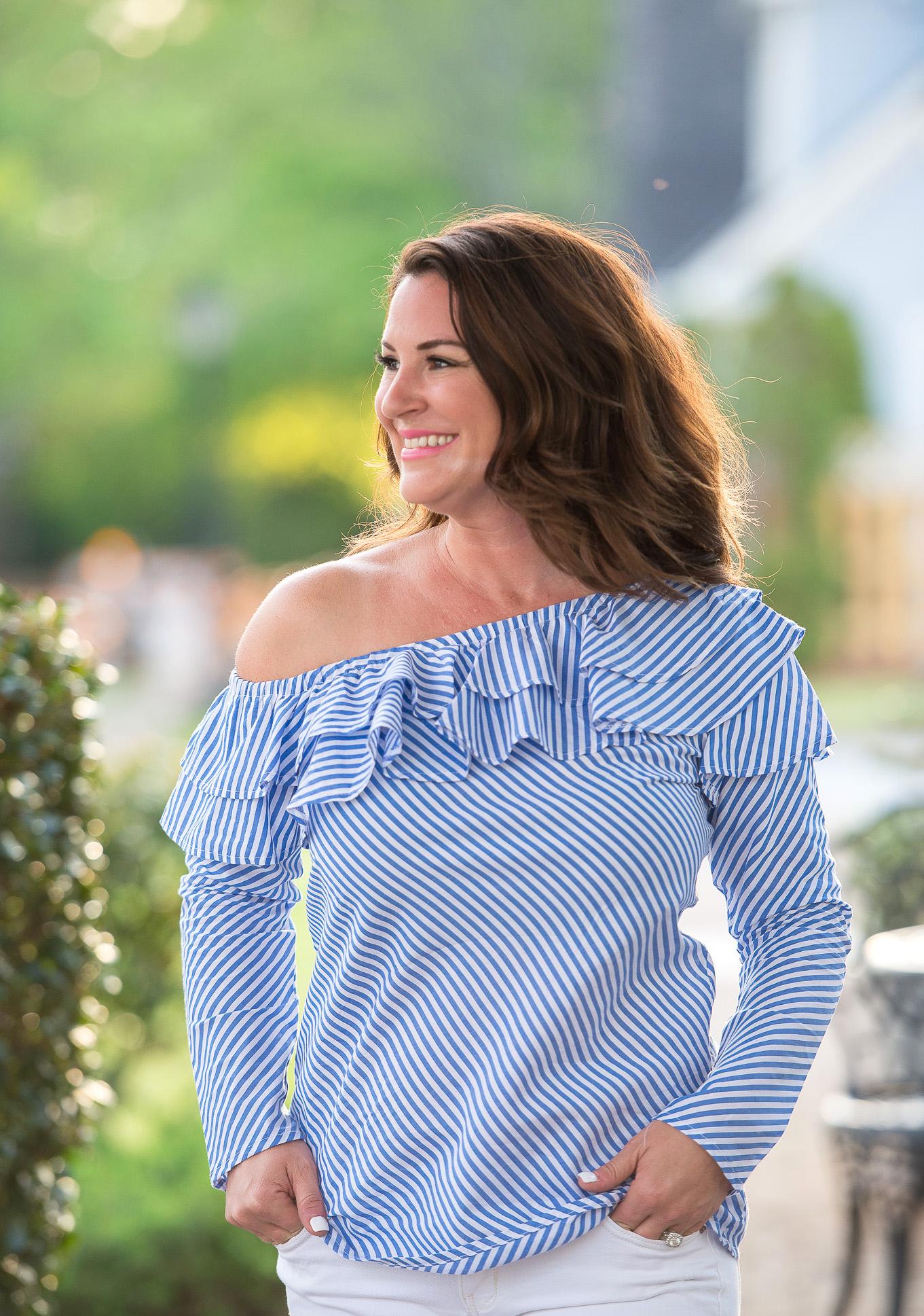 Kim Bishop in a blue striped ruffle one shoulder top